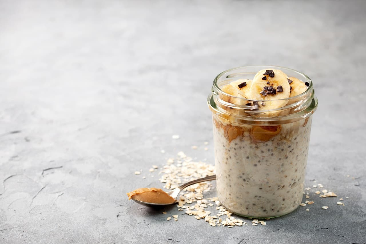 overnight oatmeal with chia seeds, bananas, peanut butter, honey, chocolate sprinkling in a glass jar
